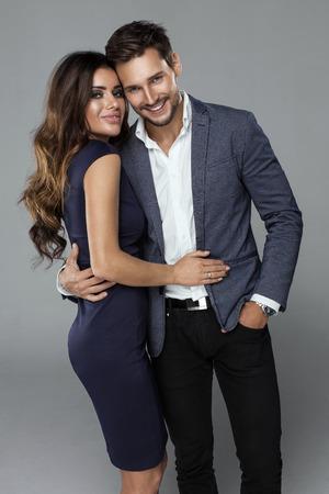 아름다운 미소 커플의 초상화. 그의 여자 친구를 포옹 재킷에 잘 생긴 남자