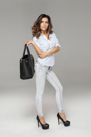 women jeans: Sexy woman with bag thinking