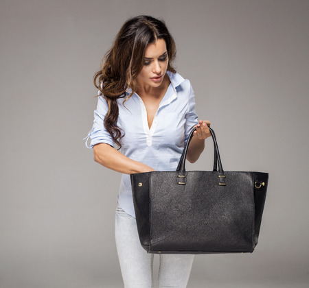 Brunette woman looking for something in her bag
