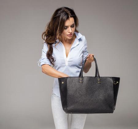 Brunette vrouw op zoek naar iets in haar tas Stockfoto - 48374185