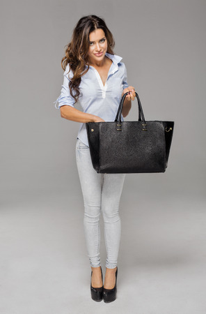woman bag: Beautiful happy woman looking for something in her bag
