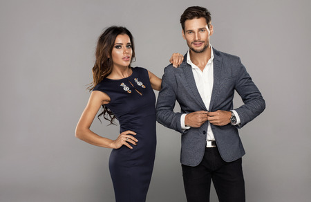 Portrait of young handsome man buttoning jacket with beautiful young woman. Beautiful couple in fashionable clothes Stock Photo