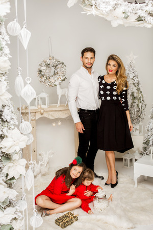 baby open present: Beautiful Family in Christmas Scenery.
