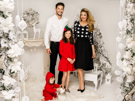 christmas scenery: Beautiful smiling family celebrating a Christmas. Beautiful Family in Christmas Scenery