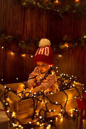christmas fun: Cute child sitting in box and wrapped in Christmas lights Stock Photo