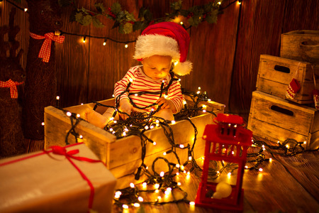 cute child: Cute child in Santa Hat sitting in box and playing with Christmas lights