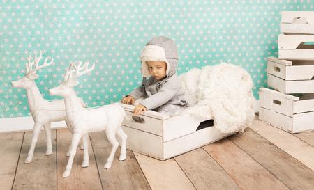 baby sit: Cute child sitting in white box wearing aviator hat