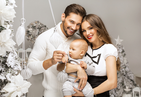 baby open present: Beautiful happy familly hugging cute child in Christmas scenery