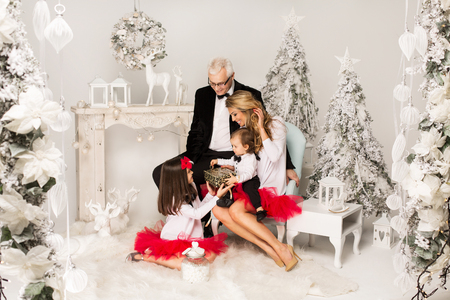 baby open present: Beautiful Family in Christmas Scenery. Smiling Parents and Children Stock Photo
