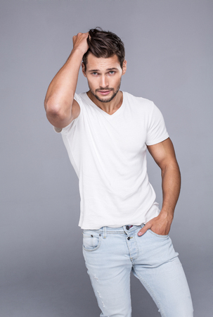 Handsome man touching his hair. Fashion model posing in white t-shirt looking at camera and touching his hair Archivio Fotografico
