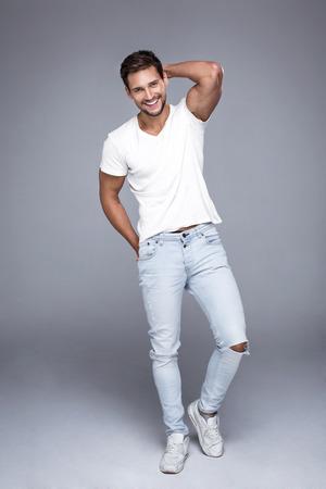 modelos hombres: Hombre sonriente hermoso que desgasta los pantalones vaqueros y camiseta blanca. Foto natural puro del hombre natural con sonrisa perfecta Foto de archivo