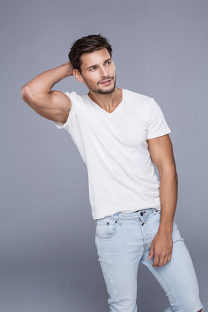 male models: Attractive man touching his hair. Fashion model posing in white t-shirt