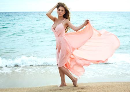 beaux seins: Belle femme inhabituelle de marcher sur la plage et en posant en robe rouge Banque d'images