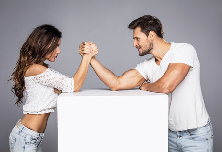 muscles: Beautiful couple doing arm wrestling challenge