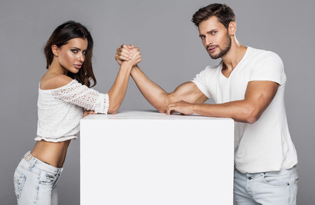 struggle: Beautiful couple doing arm wrestling challenge