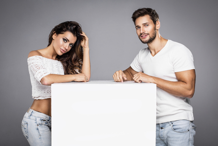 Beautiful fashion models posing on grey background with white box. White space for your advertisement.
