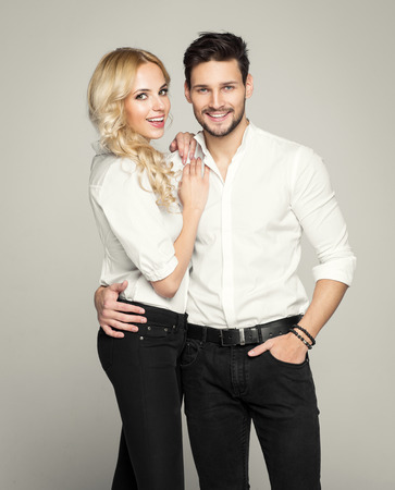 Fashionable couple in white shirt, posing on grey background