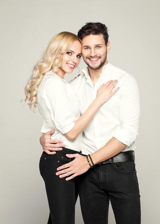 blanc: Couple mode en chemise blanche, posant sur fond gris