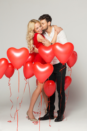 Happy valentines day: Kissing couple posing on grey background with balloons heart. Valentines day.