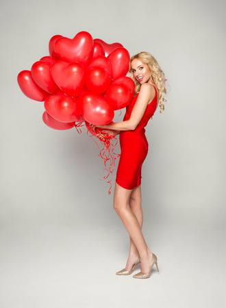 adult valentine: Beautiful blond woman posing on grey background in red dress, holding balloons heart. Valentines day.