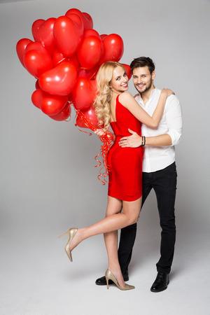 pareja enamorada: hermosa pareja feliz posando sobre fondo gris y que sostiene los globos del corazón. Día de San Valentín.