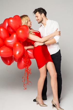 Bella pareja feliz mirando el uno al otro y que sostiene los globos del corazón. Día de San Valentín. Foto de archivo - 51693099
