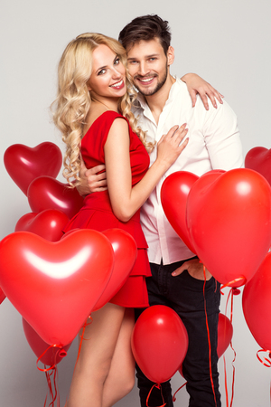 Portrait of smiling couple with balloons heart, isolated on grey background Stockfoto