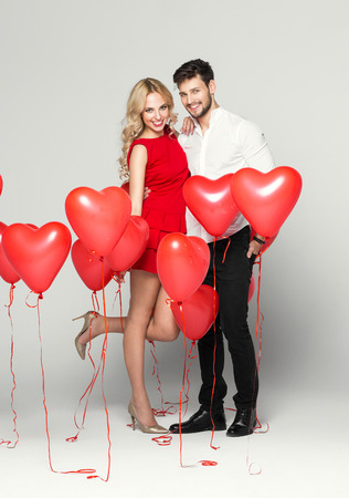 Young couple posing on grey background with balloons