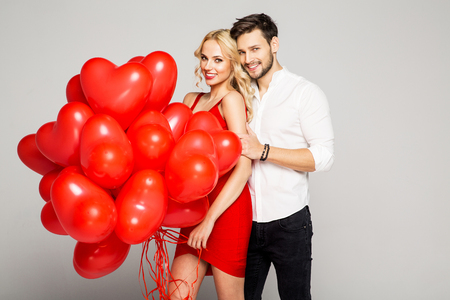 Portrait of attractive young couple posing on grey background and holding balloons heart. Valentines day.