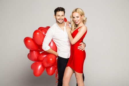 Portrait of attractive young couple posing on grey background and holding balloons heart. Valentine's day. Stockfoto