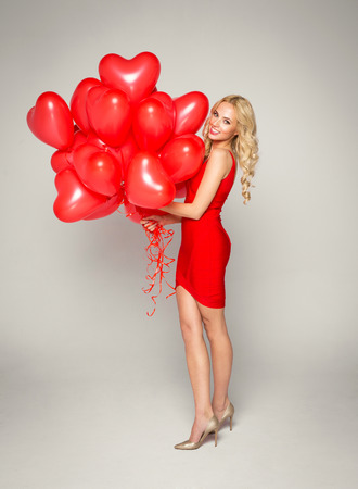 blonde woman: Beautiful blond woman posing on grey background in red dress, holding balloons heart. Valentines day.