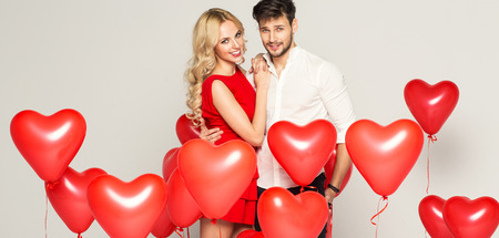 romantic: Fashionable couple with ballons heart hugging at each other Stock Photo