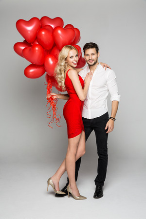 灰色の背景にポーズと風船心を持って美しい幸せなカップル。バレンタインの日。