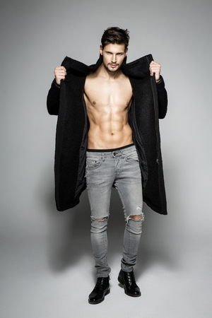 undressed: Fashion undressed man showing his chest in black coat