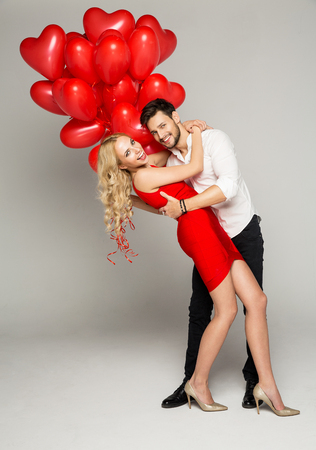 Happy beautiful couple posing on grey background and holding balloons heart. Valentines day.