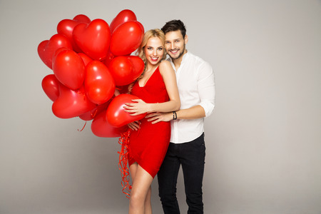 smiling face: Happy beautiful couple posing on grey background and holding balloons heart. Valentines day.