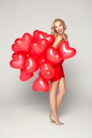 Hermosa mujer rubia sonriente que presenta en fondo gris y que sostiene los globos del corazón. Día de San Valentín.