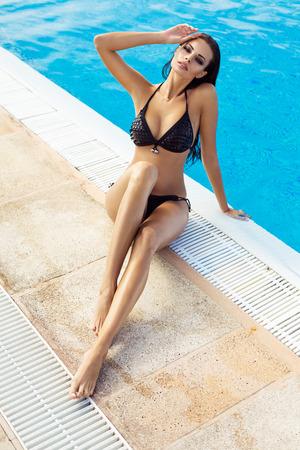 Beautiful model wearing black bikini by the pool 版權商用圖片