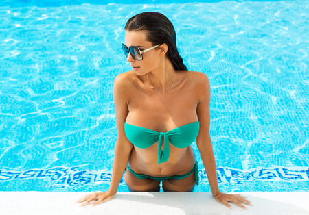 mojada: Retrato del modelo atractivo en la piscina con gafas de sol