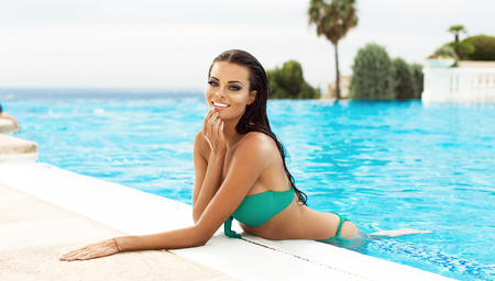 Beautiful smiling model in the pool in summer scenery