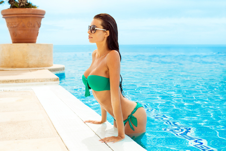 Fashion model in swimming pool wearing swimsuit and sunglasses