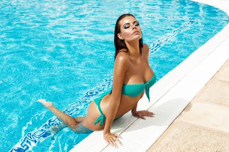 mojada: Sexy modelo en bikini en la piscina