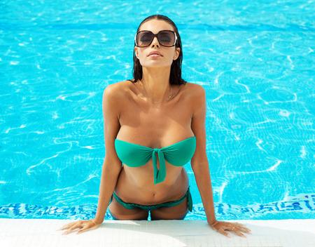 Portret van sexy model in het zwembad draagt een zonnebril Stockfoto
