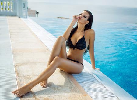 Mooie vrouw, gekleed in zwarte bikini bij het zwembad in de zomer landschap