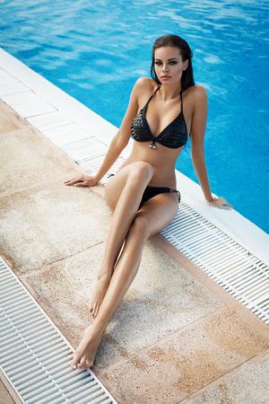 mojada: Hermosa mujer vistiendo bikini negro en la piscina