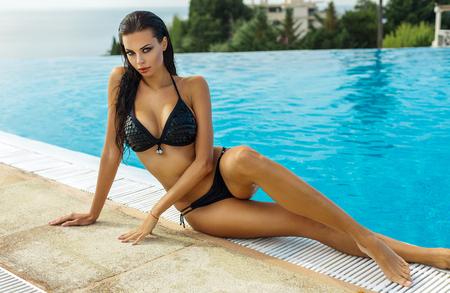 sexy füsse: Schöne Frau, die schwarze Bikini im Sommer Landschaft am Pool tragen Lizenzfreie Bilder