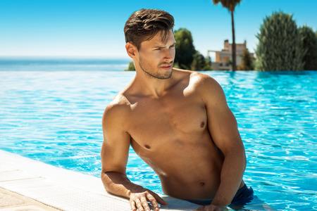Sexy Male Model Posing In Swimming Pool Stock Photo