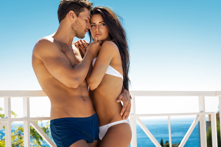 bikini couple: Sexy couple touching at each other outdoor in summer scenery Stock Photo
