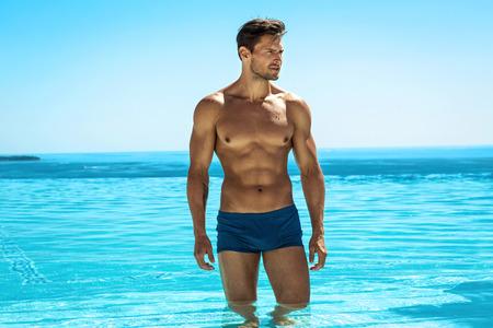 Jonge knappe man die zich voordeed in het zwembad Stockfoto