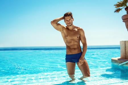 nudo maschile: Estate fotografia dell'uomo muscolare sorridente in piscina nuoto Archivio Fotografico